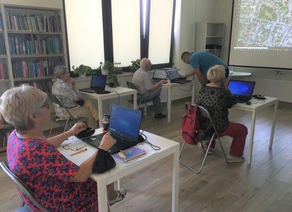 seniorzy iprowadzący podczas korepetycji wczytelni biblioteki głównej