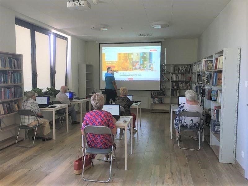 seniorzy i prowadzący podczas korepetycji w czytelni biblioteki głównej