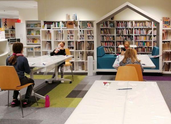 zdjęcie przedstawiające uczestników zajęć pracujących nadswoimi pracami scrapbookingowymi