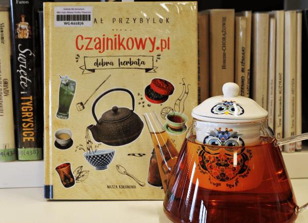 """Zdjęcie przedstawia książkę Rafała Przybyloka """"Czajnikowy.pl - dobra herbata"""" oraz szklany czajniczek z wizerunkiem sówki a w nim czerwona herbata. Książkę można wypożyczyć w Bibliotece Głównej w Piasecznie."""