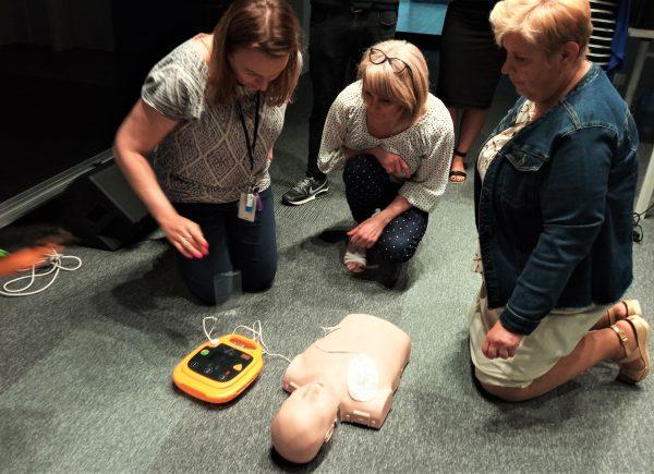 Pracownicy uczą się jak korzystać zdefibrylatora.