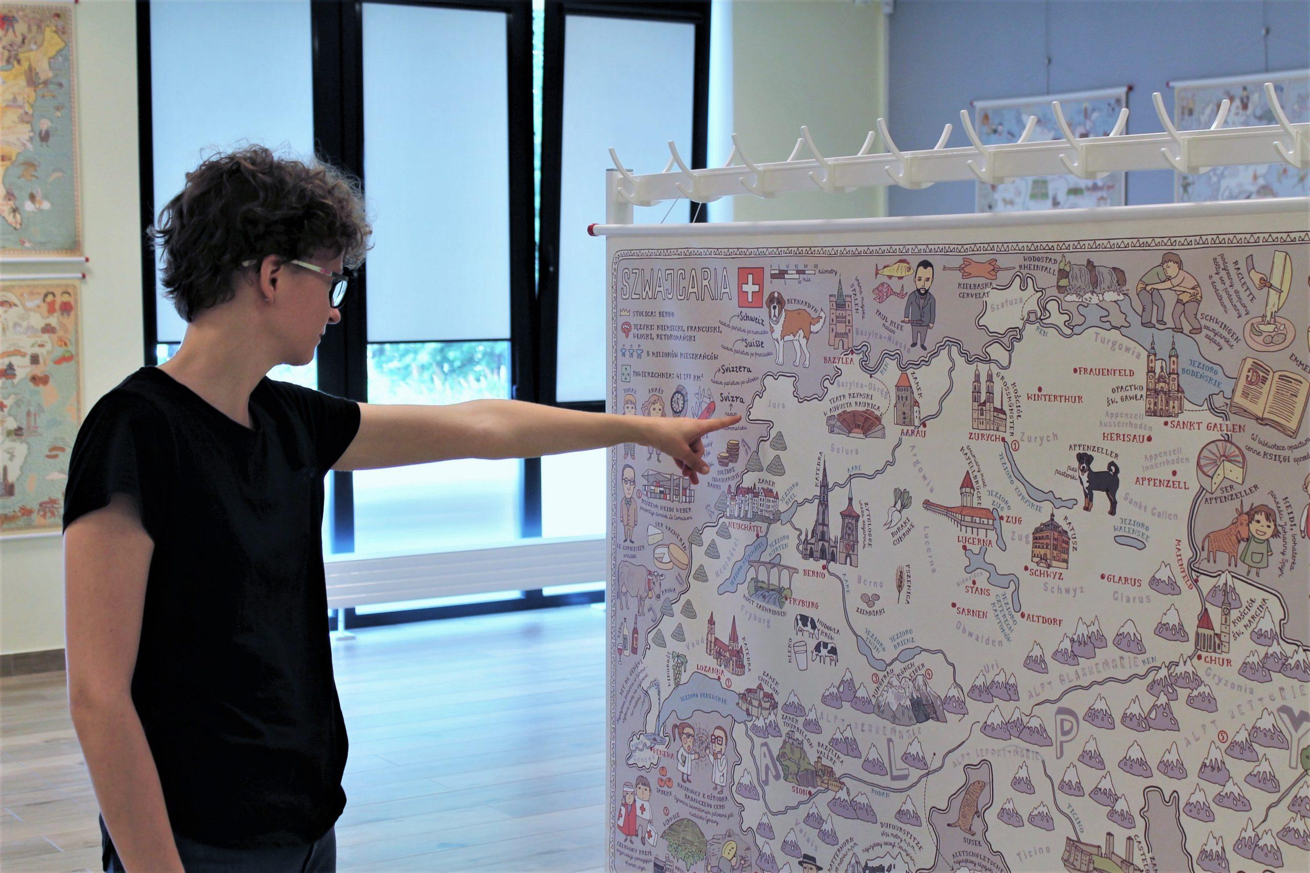 """Zwiedzający ogląda wystawę """"Mapy"""" wsali wystawowej Biblioteki Głównej wPiasecznie"""