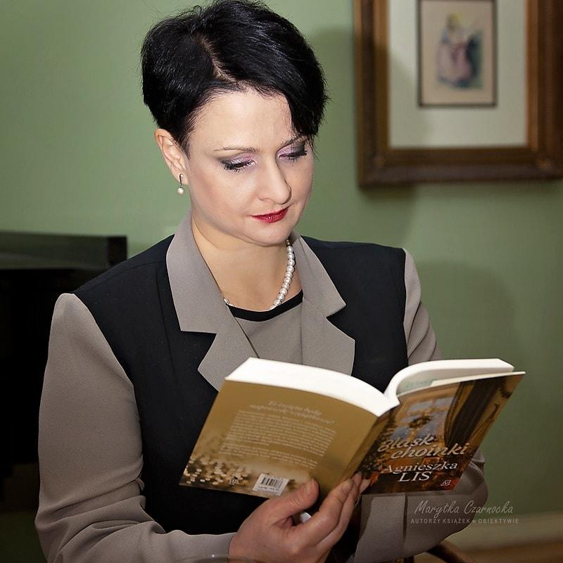 Agnieszka Lis trzymająca wrękach książkę.