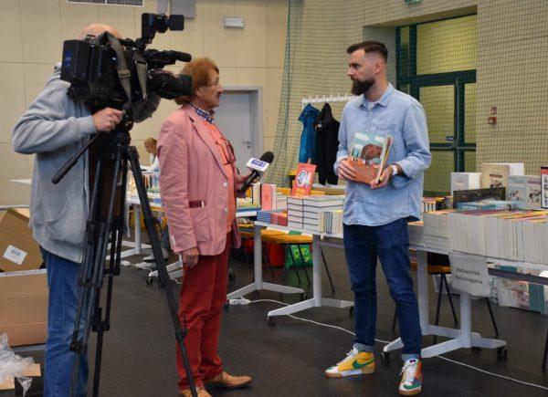Reporter trzyma wręku mikrofon irozmawia zwydawcą książek. Wtle widać kamerzystę, którynagrywa tę scenę.