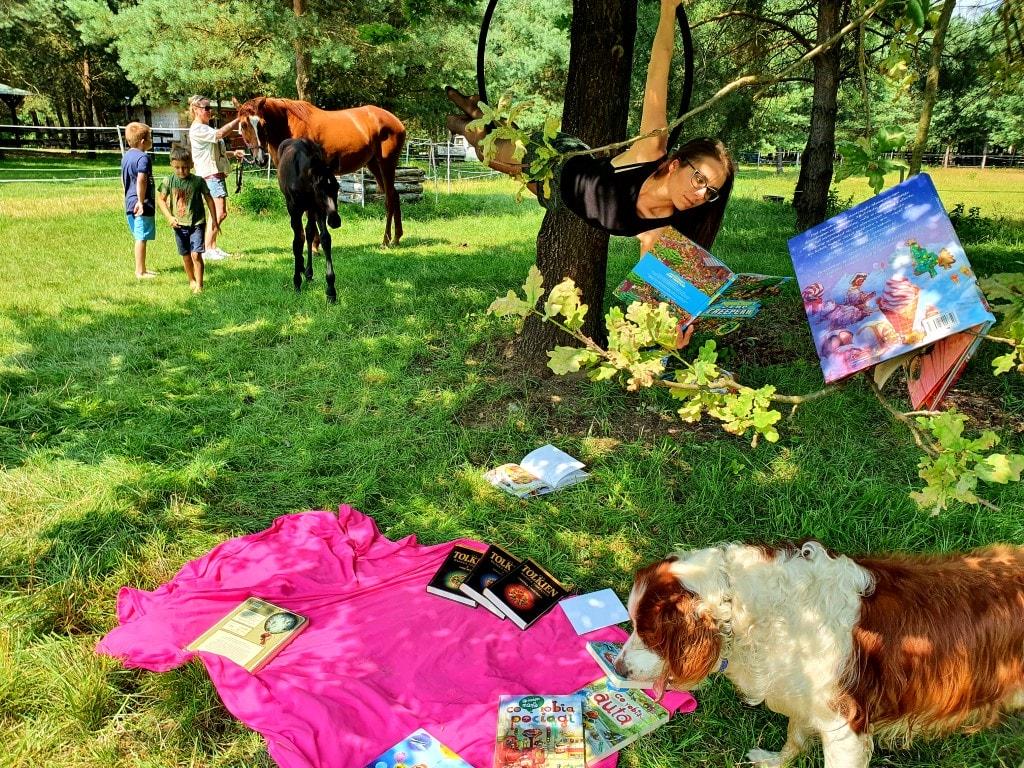 Na zdjęciu widać bajkową scenerię. Kobieta wisi naobręczy iczyta książkę. Nafotografii znajdują się: konie, pies idziecko. Dziecko czyta książkę nakocu. Jedna publikacja jest zawieszona nadrzewie.