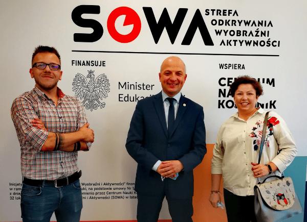 Dyrektor biblioteki Łukasz Załęski z Sylwią Chojnacką-Tuzimek i Danielem Putkiewiczem stoją i pozują do zdjęcia. Za nimi ścianka z banerem promującym inicjatywę SOWA.