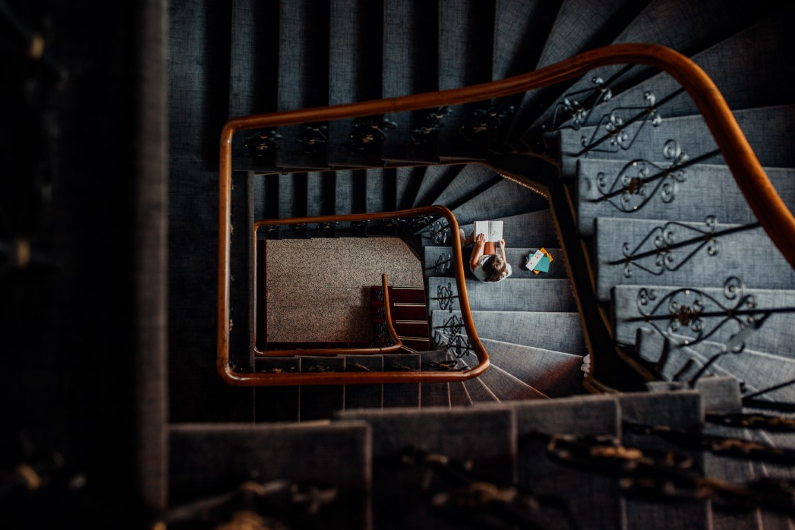 Zdjęcie przedstawia czarne schody. Nakońcu schodów siedzi dziewczynka iczyta książkę.