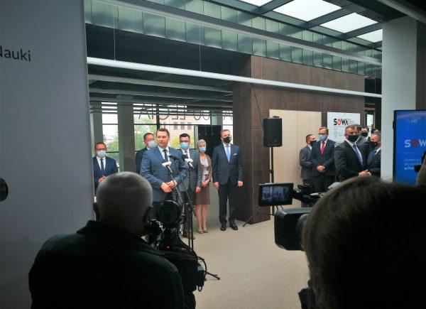 Inauguracja projektu SOWA. Przemawia Minister Edukacji iNauki Przemysław Czarnek. Zanim stoją osoby organizujące inicjatywę.