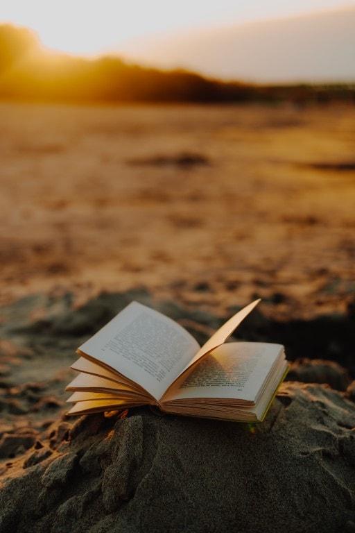 Zdjęcie przedstawia książkę leżącą nagórze usypanej zpiasku. Wtle zachód słońca.