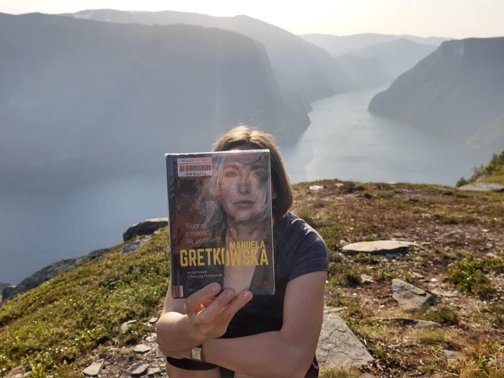 Zdjęcie przedstawia kobietę. Trzyma ona książkę, którazasłania jej twarz (sleeveface). Wtle góry.