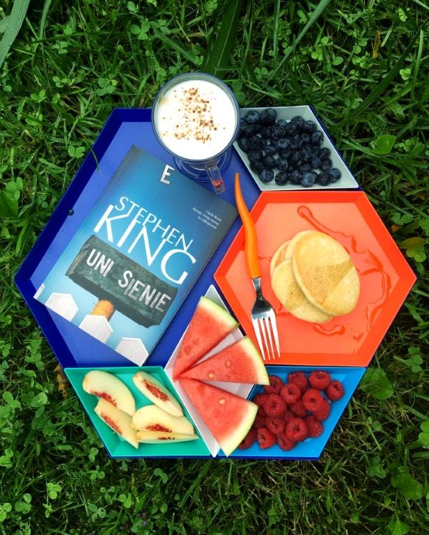 Zdjęcie przedstawia tackę zjedzeniem - borówkami, naleśnikami, malinami, arbuzem, brzoskwinią. Wnajwiększej przegrodzie leży książka zkawą. Wtle trawa.