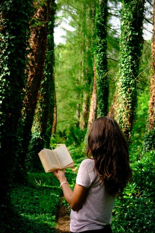 Na zdjęciu dziewczynka czytająca książkę wlesie.