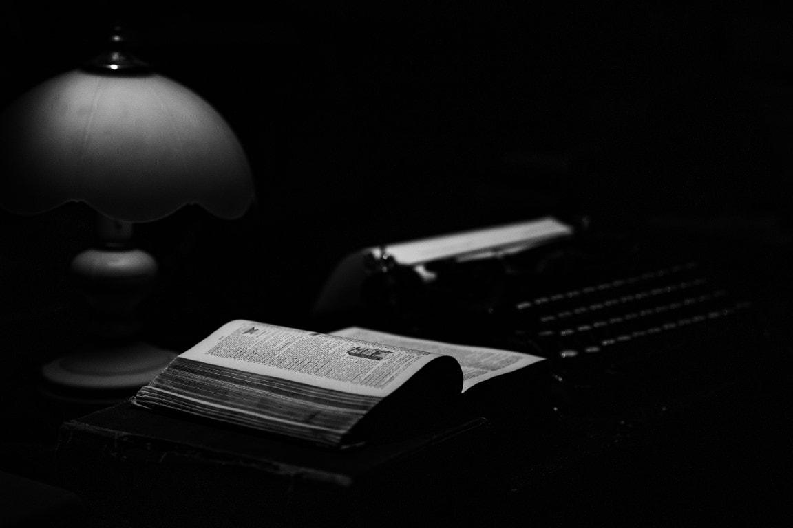 Na zdjęciu widać maszynę dopisania, książkę ilampkę. Fotografia jest czarno-biała.