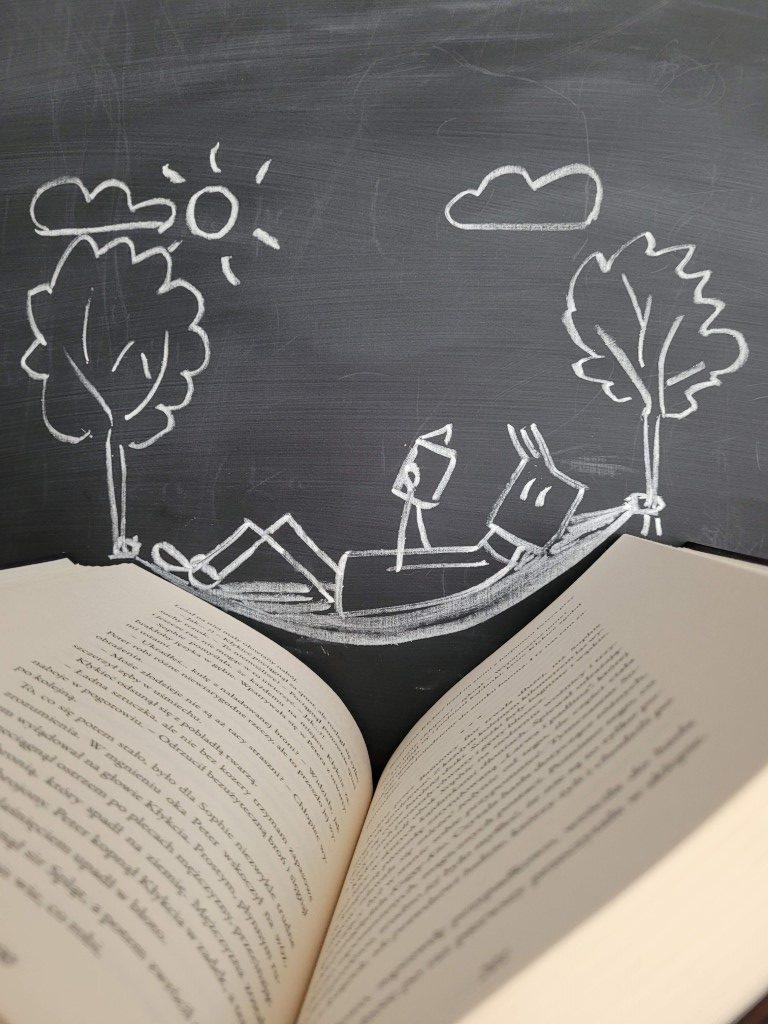 Zdjęcie przedstawia książkę. Wtle czarna tablica ananiej narysowany ludzik nahamaku zawieszonym nadrzewach.
