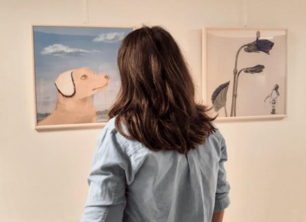 """Zdjęcie przedstawia kobietę, która ogląda wystawę """"Abecadło""""."""