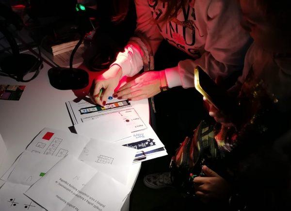 Na zdjęciu widać ręce uczestników. Jeden znich wskazuje nakartę zzadaniem. Pomieszczenie jest oświetlone naniebiesko.