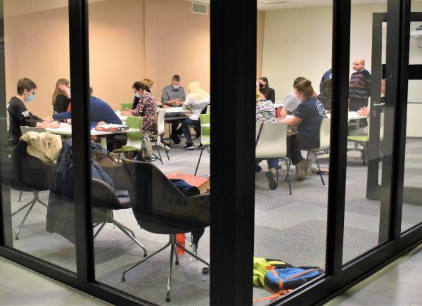 Zdjęcie przedstawia uczestników wydarzenia biorących udział wrozgrywkach gry Rummikub. Uczestnicy siedzą przy stolikach igrają wgrę.