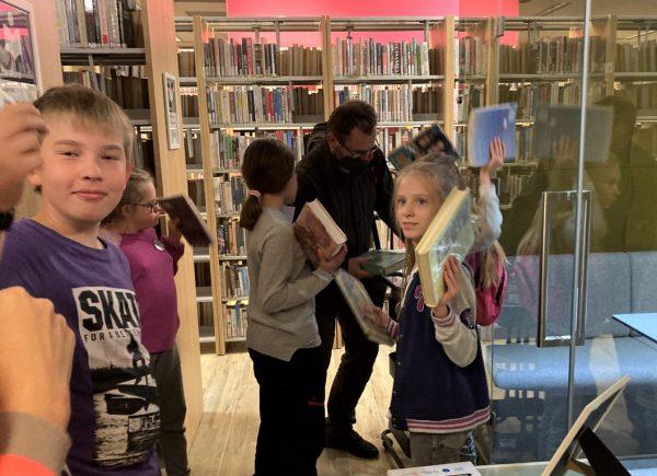 """Na zdjęciu widać uczestników wydarzenia """"Noc bibliotek!"""" Dzieci trzymają wrękach książki."""