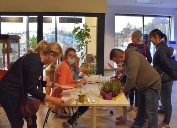 """Na zdjęciu widać uczestników """"Nocy bibliotek!"""" iorganizatorkę wydarzenia Urszulę Bąkowską. Uczestnicy podpisują wymagane dokumenty."""