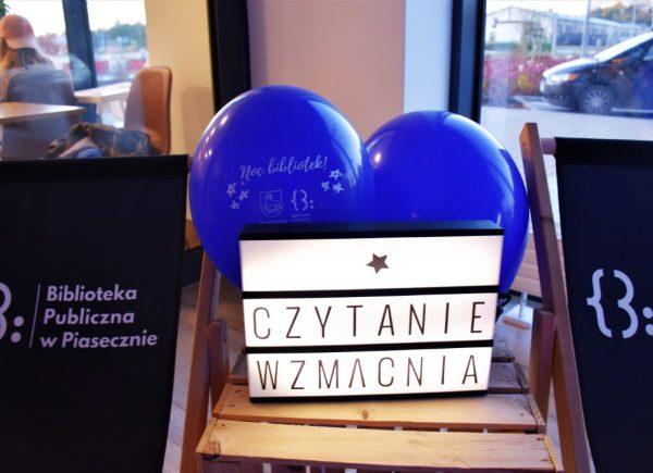 """Na drewnianym krześle widać dwa niebieskie balony znapisem: """"noc bibliotek!"""". Przedbalonami umieszczono świecącą nabiało tabliczkę zczarnym napisem: """"Czytanie wzmacnia"""". Poobydwu stronach krzesła można dostrzec czarne leżaki zlogo biblioteki."""