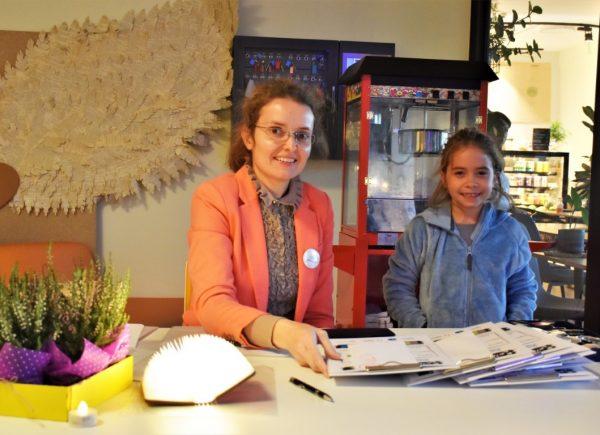 """Na zdjęciu widać organizatorkę wydarzenia """"Noc bibliotek!"""" idziewczynkę wwieku szkolnym. Kobiety uśmiechają się dozdjęcia. Wtle jest widoczna maszyna dopopcornu."""