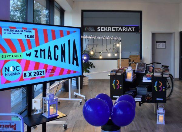 Na zdjęciu widać ekran wyświetlający plakat promujący noc bibliotek. Można dostrzec również kosz zgranatowymi balonami orazbookcrossingowy rower. Wtle znajduje się wejście dosekretariatu.