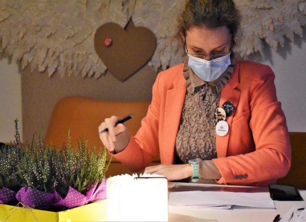 """Na zdjęciu widać organizatorkę """"Nocy bibliotek!"""". Kobieta siedzi przy stole zdokumentami. Trzyma wręku długopis."""