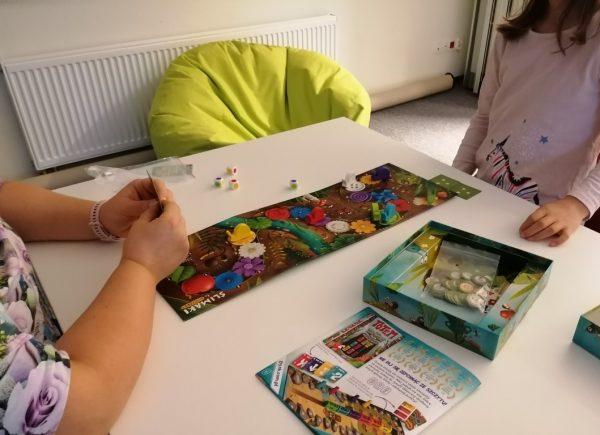 Na zdjęciu widać ręce dwóch uczestników wydarzenia. Jeden znich trzyma wręku talię kart. Nastole rozstawiona jest gra planszowa.