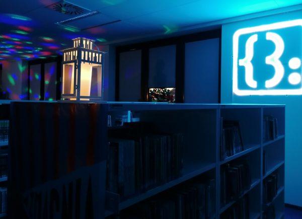 Na zdjęciu widać regały zksiążkami. Pomieszczenie jest oświetlone naniebiesko.