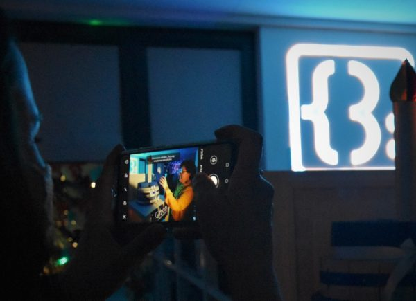 Na zdjęciu widać organizatorkę robiącą zdjęcie. Pomieszczenie jest oświetlone naniebiesko.
