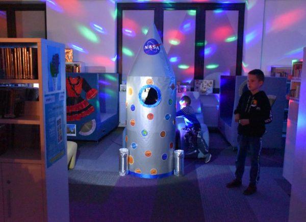 Na zdjęciu widać rakietę fotobudkę. Jest ona oświetlona kolorem niebieskim. Wtle można dostrzec dzieci.