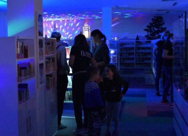 Na zdjęciu widać uczestników wydarzenia. Stoją oni między regałami. Pomieszczenie jest oświetlone naniebiesko.