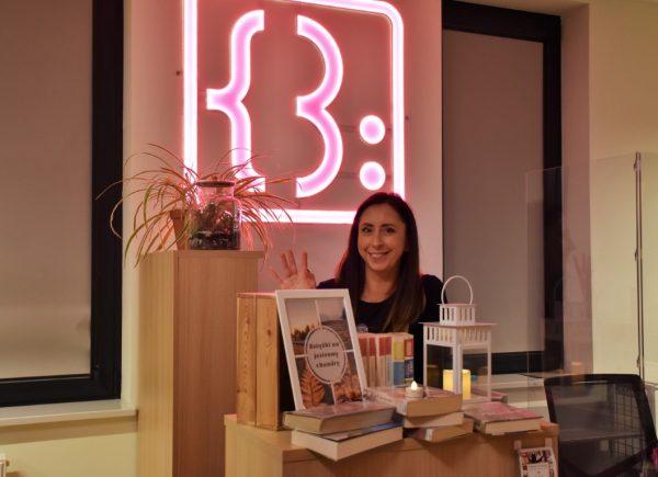 Na zdjęciu widać organizatorkę wydarzenia Edytę Dryję. Kobieta macha iuśmiecha się dofotografa, któryrobi jej zdjęcie. Przednią stoi stos książek izapalony lampion.