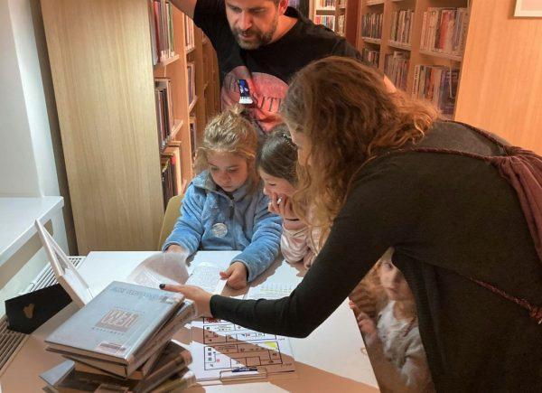 Na zdjęciu widać czteroosobową rodzinę. Mężczyzna przytrzymuje się ręką oregał zksiążkami. Dwie dziewczynki rozwiązują karty zzadaniami. Kobieta pochyla się nadnimi iim pomaga.