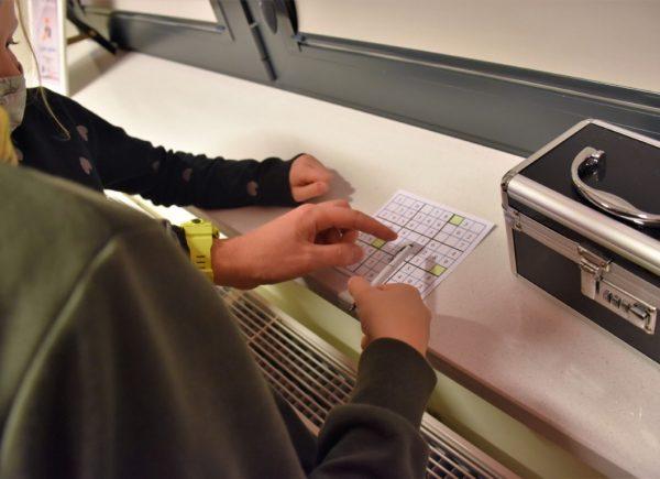 Na zdjęciu widać ręce uczestników. Jeden znich palcem wskazuje nakartę zzadaniem dowykonania. Poprawej stronie fotografii można dostrzec czarną skrzynkę.