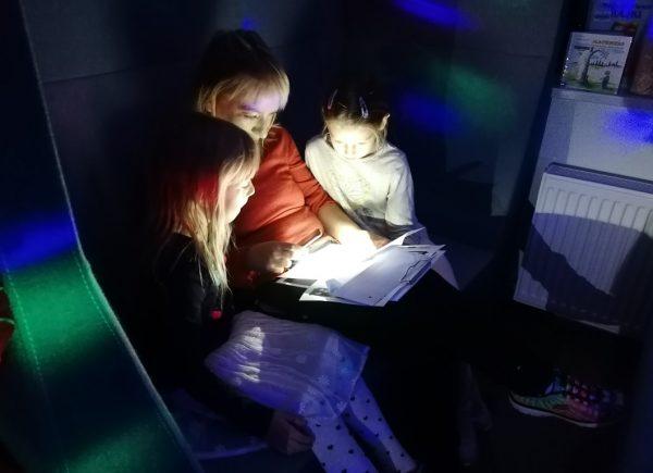 """Na zdjęciu widać uczestników """"Nocy bibliotek!"""". Rozwiązują oni zadanie, siedząc nasofie. Pomieszczenie jest oświetlone naniebiesko."""