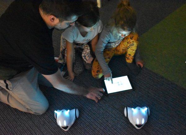 Zdjęcie przedstawia mężczyznę idwoje dzieci. Jedna zdziewczynek uruchamia poprzez tablet robota edukacyjnego.