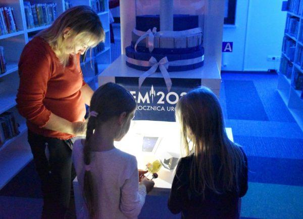 Na zdjęciu widać kobietę zdwiema dziewczynkami. Dzieci rozwiązują zadanie. Pomieszczenie jest oświetlone naniebiesko.