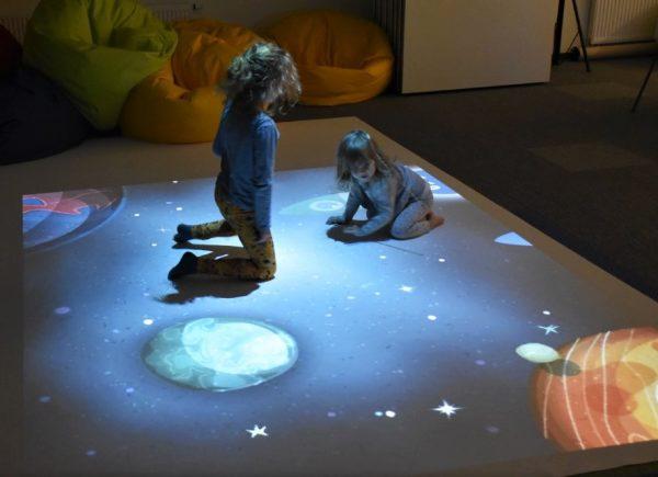 Na zdjęciu widać dwie dziewczynki, które grają wgrę napodłodze multimedialnej.