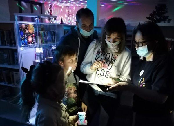 """Na zdjęciu widać uczestników """"Nocy bibliotek!"""". Rozwiązują oni zadanie. Pomieszczenie jest oświetlone naniebiesko."""