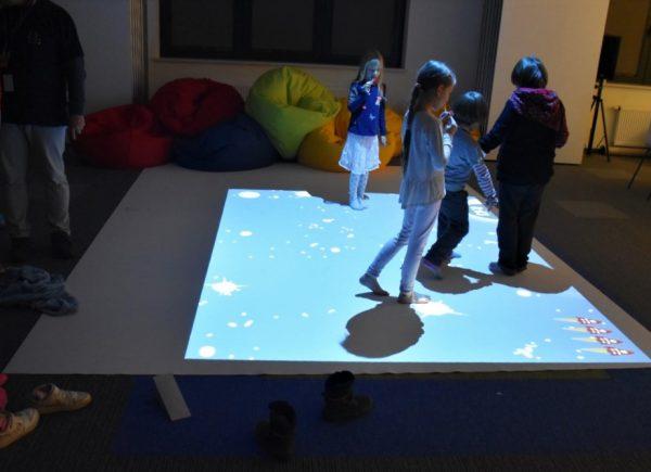 Na zdjęciu widać dzieci, które grają wgrę napodłodze multimedialnej.