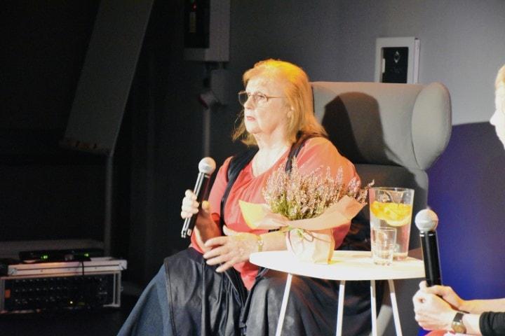 Stanisława Celińska siedzi nafotelu nascenie. Trzyma wręku mikrofon. Patrzy wstronę publiczności.
